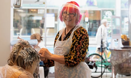 A hairdresser at Tusk hair salon in London smiles as she gets back to work on 4 July