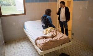 """Psychiatrist Pedro Serra (R) speaks with a patient placed in an isolated room at the psychiatric hospital """"EPS de Ville Evrard, Centre psychiatrique du Bois de Bondy"""""""