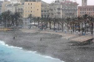 People walk through heavy snowfall along the Promenade des Anglais in Nice.