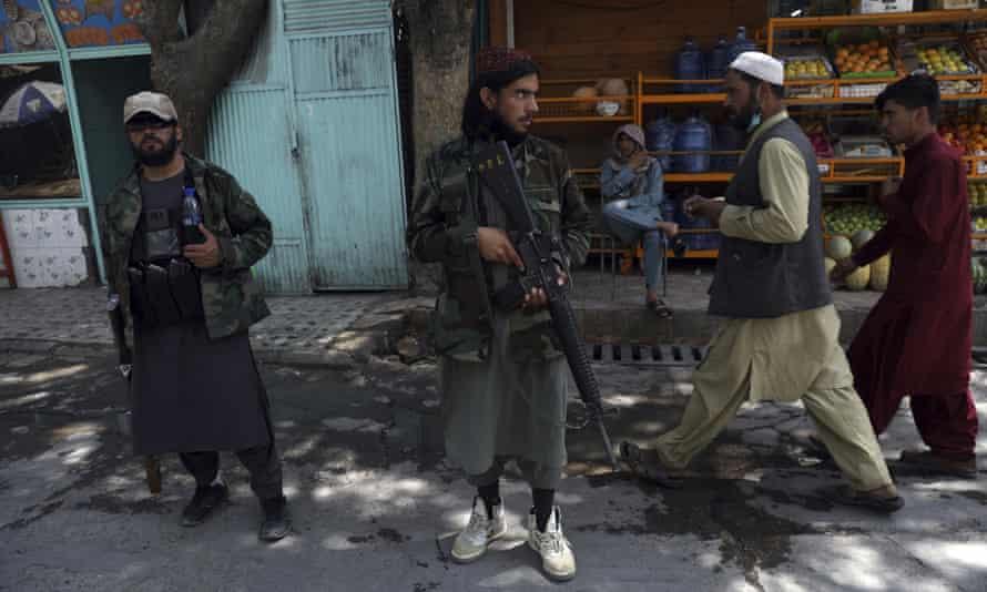 Taliban fighters stand guard at a checkpoint in the Wazir Akbar Khan neighbourhood