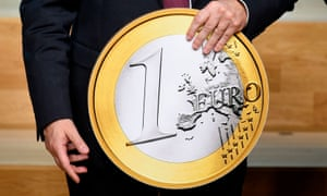 President of the ECB, Mario Draghi, holds a replica of a euro