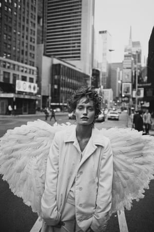 Amber Valletta in white and with large white wings in a New York street
