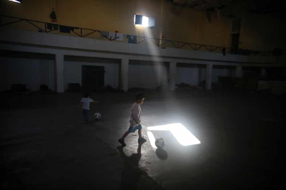 Antonio, a five-year-old boy from Guatemala, plays football in a shelter for immigrants in an abandoned cinema in Mexicali.