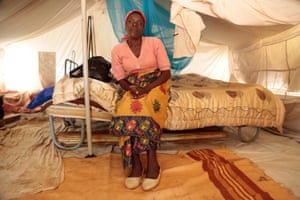 Chipo Ruwo sits on a bed in her tent in a makeshift camp in Chimanimani, Zimbabwe