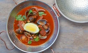 Clams with tomato, chorizo and coriander in a stainless steel bowl