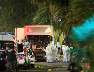 Police and forensic officers stand next to the truck that ran into a crowd celebrating Bastille Day along a beachfront esplanade