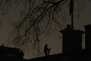In Washington, a US secret service counter-sniper stands on the roof of the White House