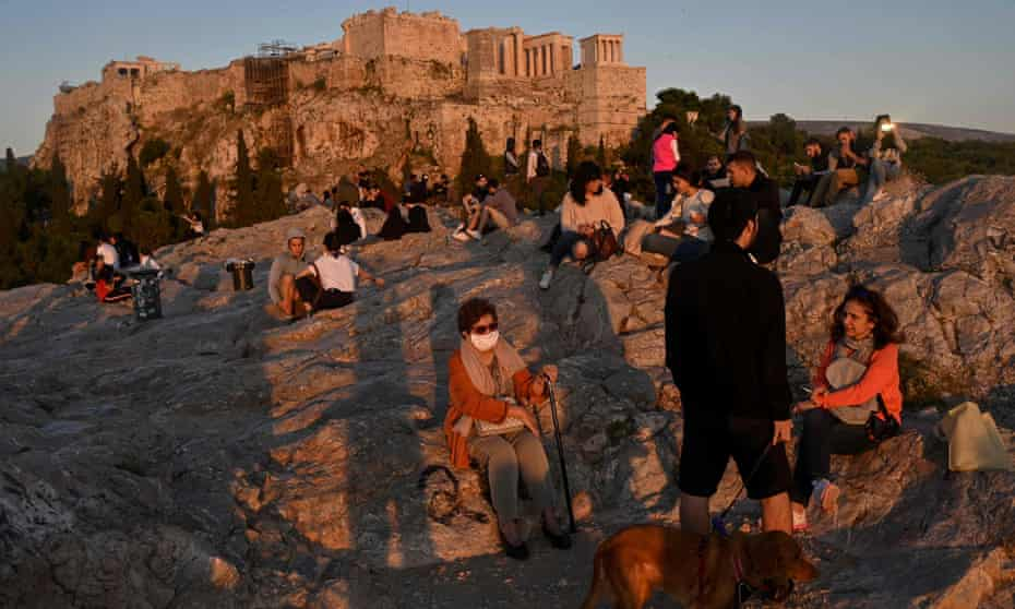 People enjoy a sunset in the Aeropagus hill overlooking the Ancient Acropolis in Athens as Greece gradually eases its lockdown against the spread of the COVID-19, the novel coronavirus, lifting up most of the restrictions on citizens' movement.