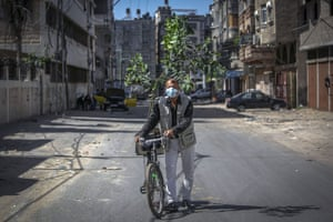 A man wearing a protective mask carries a tree sapling on his bicycle in Gaza city on Monday