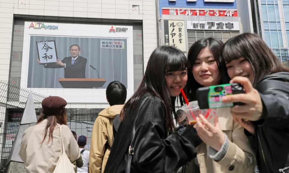 Young women take selfies as a large screen broadcasts Yoshihide Suga