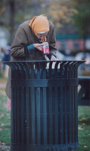 An elderly woman finds something to eat and drink in a garbage can on York Quay, Toronto.