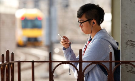 A commuter uses a mobile phone while wearing headphones at Central Station in Sydney, Australia