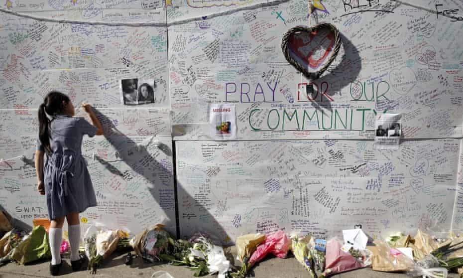 A schoolgirl writes a message on a wall for victims and survivors of the Grenfell Tower fire