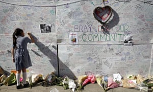 A schoolgirl writes a message on a wall for the victims of the Grenfell Tower fire.