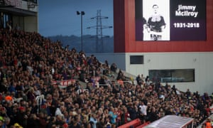 Fans pay tribute to Jimmy McIlroy during a match.