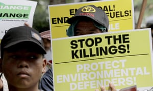 Environmental activists hold placards during a rally outside in Quezon city, north-east of Manila