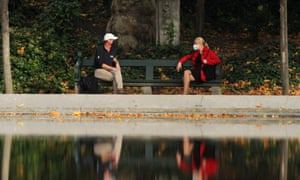 People wearing face masks talk while maintaining social distance in a park in Brussels, Belgium