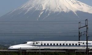 A shinkansen bullet train travels past Mount Fuji in Japan