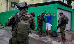 Brazilian army soldiers frisk a resident during a joint operation in the Cidade de Deus (City of God) favela.
