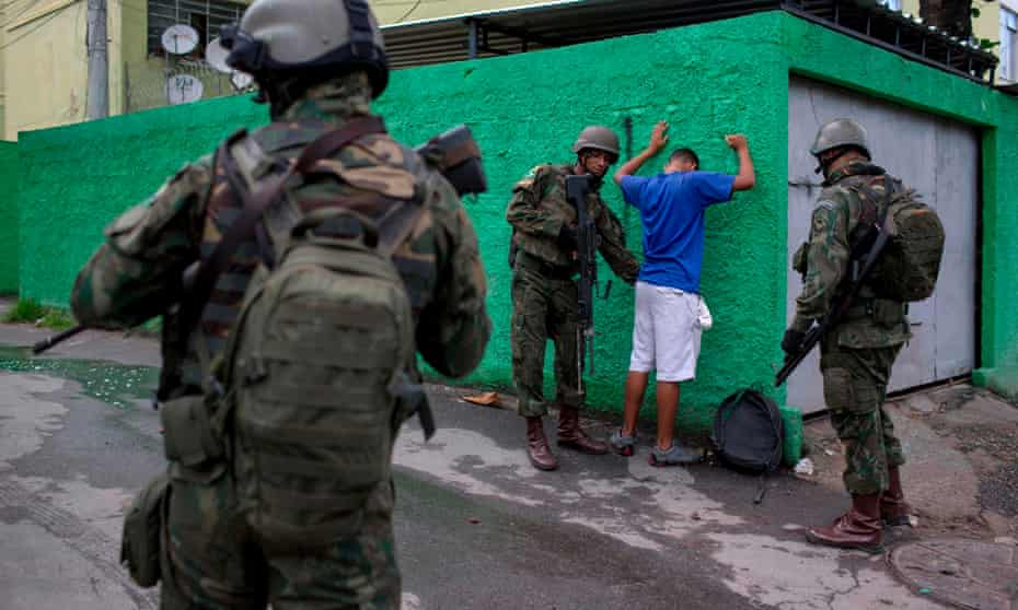 Brazilian soldiers frisk a resident during an operation in the City of God favela in Rio de Janeiro, Brazil.