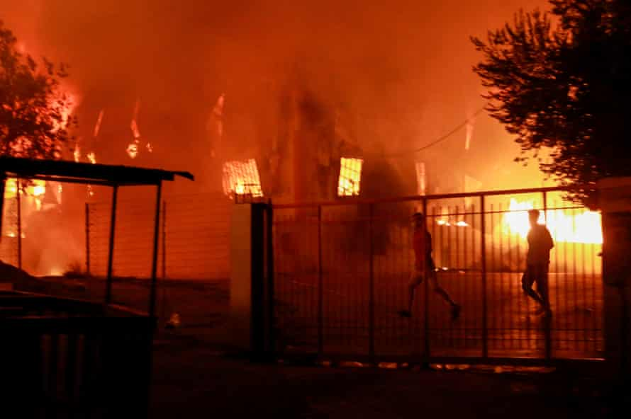 Men run to escape the fire at Moria on Wednesday