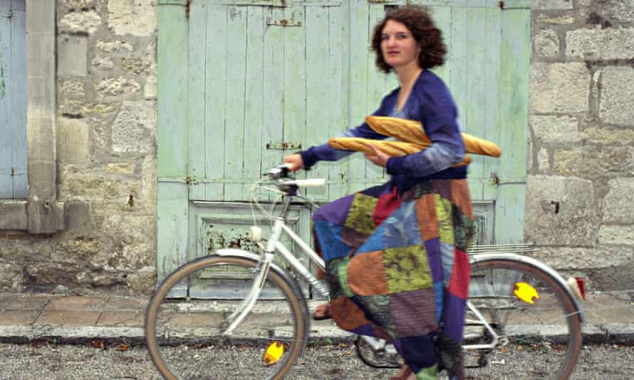 A young woman riding a bicycle past old barn doors