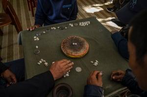 Elderly Tibetan men play a traditional game at the Caigongtang Nursing Home