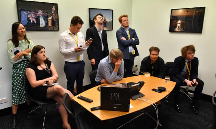 Australian Associated Press journalists look on as bureau chief Paul Osbourne holds his head after being that AAP will be closing on 26 June.