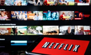 the Netflix media service provider's logo is displayed on the screen of an iPhone in front of a television screen