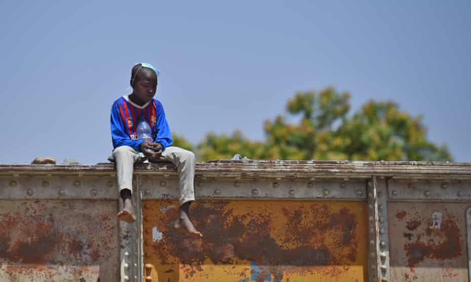 Waiting for international attention … boy in a Barcelona FC shirt in Khartoum, at the railway overpass outside army headquarters where protesters are demanding civil rights in the wake of the ousting of president Omar al-Bashir.