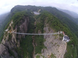 The bridge hangs precariously between the two sides of the canyon, surrounded by dramatic landscape.