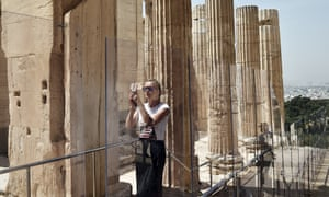 A visitor taking photos at the Acropolis in Athens