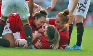 Manchester United players celebrate with their captain Katie Zelem, centre, after she had opened the  scoring against City from a free-kick.