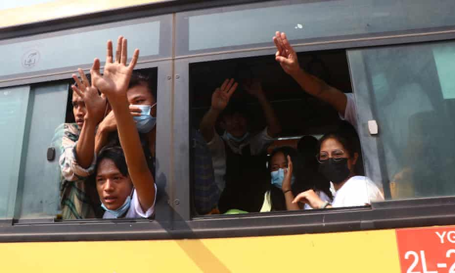 Arrested protesters wave from a bus after their release from Insein prison in Yangon