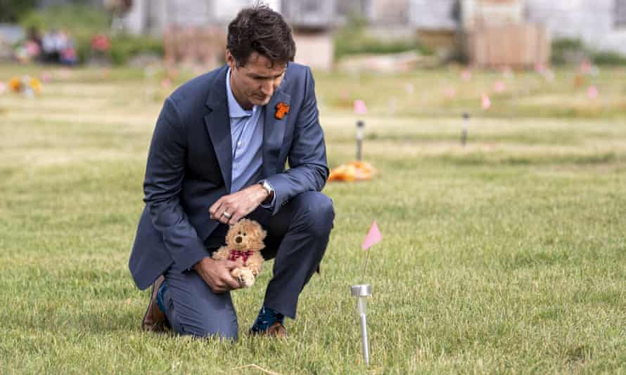 Justin Trudeau lays a teddy bear at the site of a former residential school.