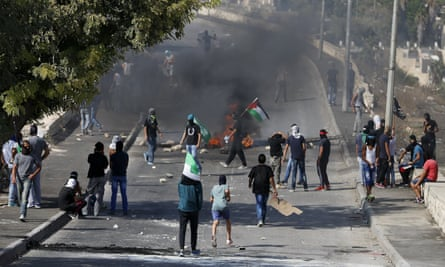 Palestinians stand near a burning barricade during clashes with Israeli security forces in the East Jerusalem neighbourhood of Issawiya.
