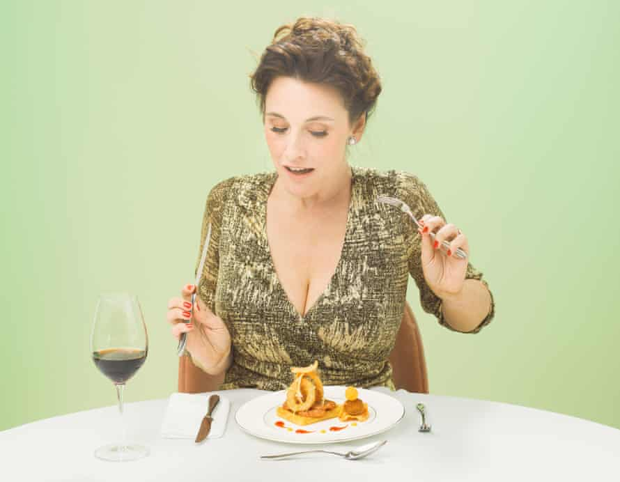 Grace Dent sitting at a table with white tablecloth, glass of red wine and a plate of food, holding up a fork