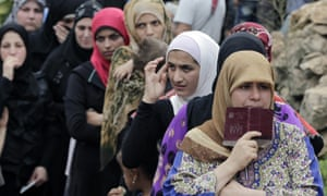 Syrian women queue to receive aid at a refugee camp in the town of Ketermaya, Lebanon.