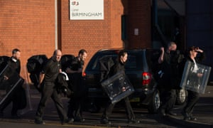 Prison staff carrying riot shields leave HMP Birmingham in Winson Green the day after the riot.