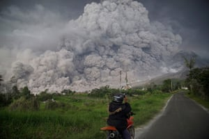 An Indonesian man takes a picture of Mount Sinabung volcano as it spews thick volcanic ash