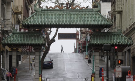 A pedestrian crosses Grant Street behind the Dragon Gate, an entrance to Chinatown in San Francisco.