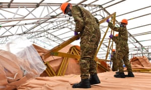 Military personnel work on the roof of the Skripal house.