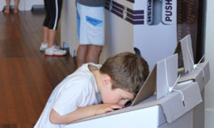A young boy looks into a ballot box in Sydney.