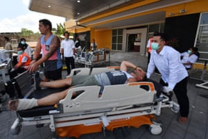 An injured foreign tourist (C) receives medical attention at a makeshift unit set up outside the Moh. Ruslan hospital in Mataram.