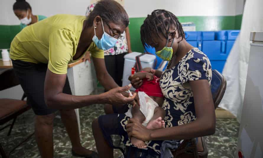 A healthcare worker vaccinates 2-year-old Michaelle Laguerre at a malnutrition clinic run by Unicef in Les Cayes, Haiti, on 26 May.