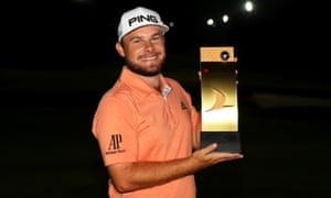Tyrrell Hatton of England poses with the trophy as darkness falls in Antalya, Turkey.