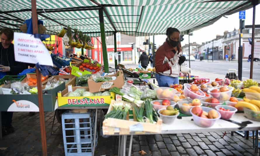 A fruit and veg stall with social-distancing signs in Newham, east London