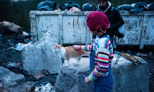 A girl pets a cat at the refugee camp in Dunkirk, France.