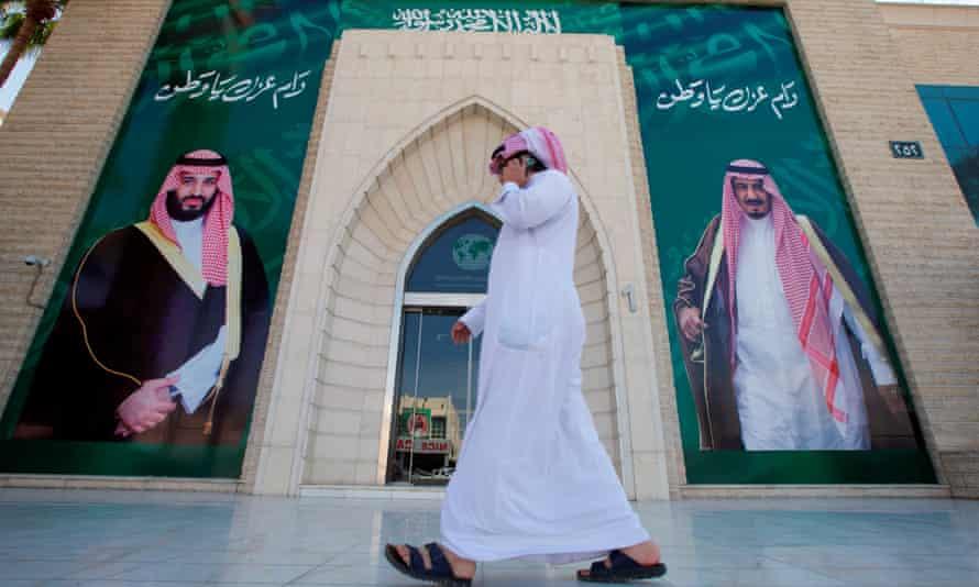 A man passes posters depicting Saudi Arabia's King Salman bin Abdulaziz Al Saud (right) and Crown Prince Mohammed bin Salman in Riyadh.