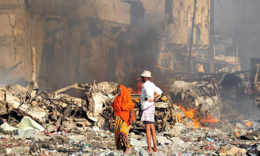 A man and woman look at the damage on the site of the explosion of a truck bomb in the centre of Mogadishu